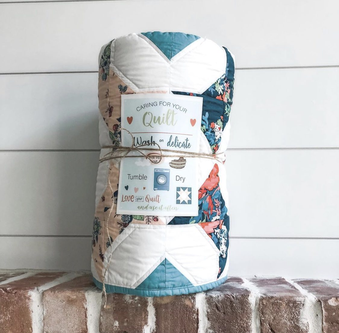 a quilt tied with ribbon with a Quilt Care Card