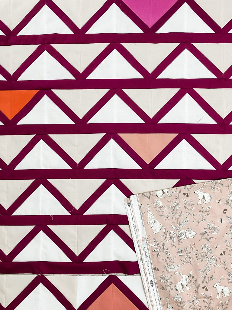 White, Cream, Pink, and orange fabric triangles that make a Cafe Tiles Quilt Top