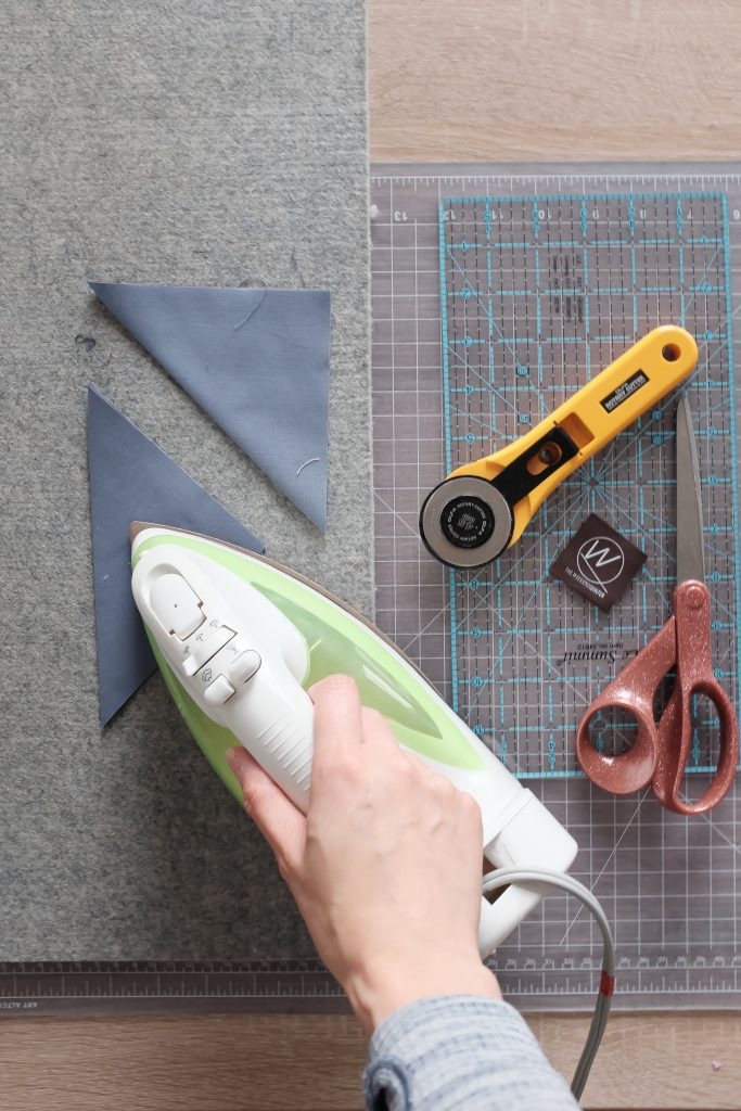 An iron pressing fabric in half, a rotary cutter, and scissors.